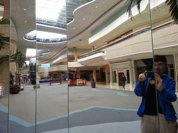 Blog author reflected in empty mall mirrors