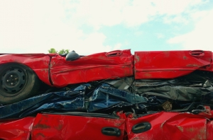three stacked, crushed cars in a junkyard