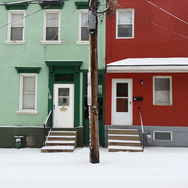 Two rowhouses in the Bloomfield neighborhood of Pittsburgh: one green, one red