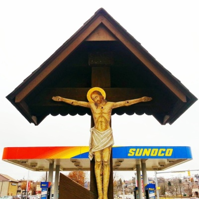 Crucifixion scene with Sunoco gas station in background