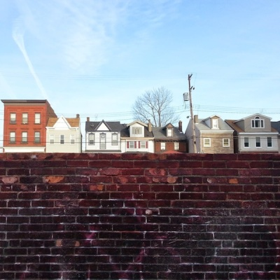 Bloomfield rowhouses seen over a wall