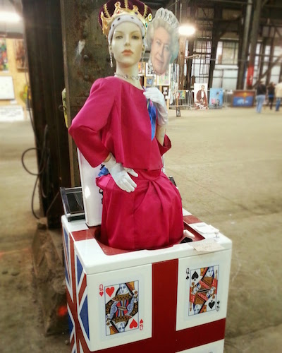 Artwork with a mannequin dressed like a queen in a clothes washing machine