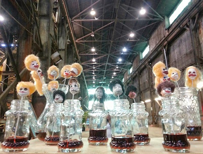 artwork with tiny clown heads on sticks in jars with mysterious liquid