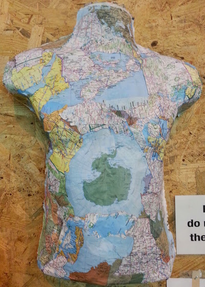 sculpture of human torso with world map glued to it
