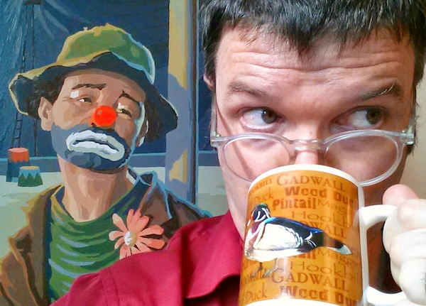 Blogger with coffee mug and sad clown painting