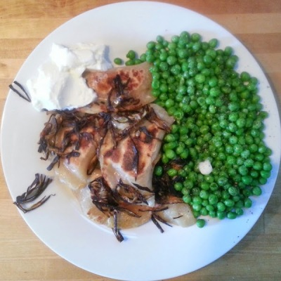 dinner plate with cooked pierogies, onions, sour cream, and green peas