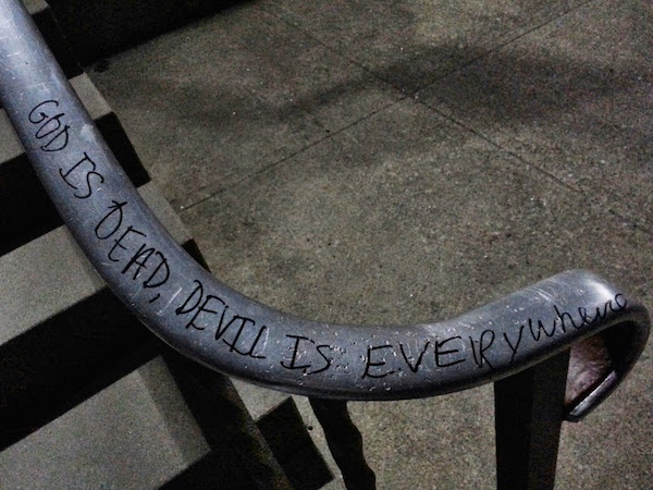 "Church stair rail with graffiti reading ""God is dead, Devil is everywhere"""