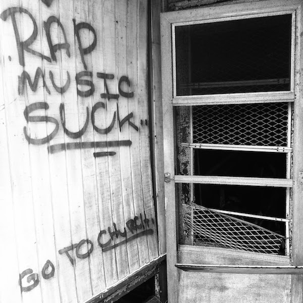 "Abandoned storefront with graffiti reading ""Rap music suck. Go to church."""