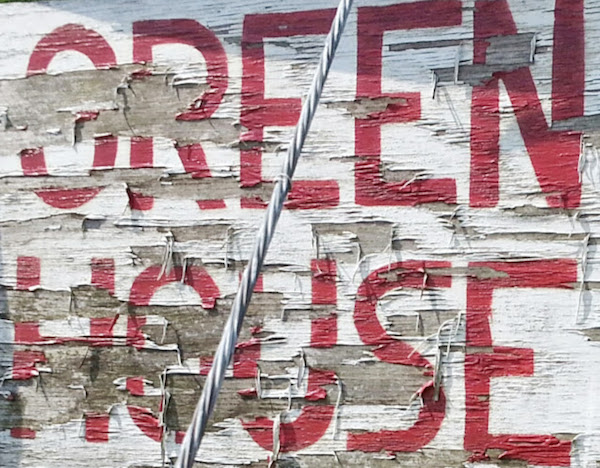 "worn painted wooden sign reading ""Greenhouse"""