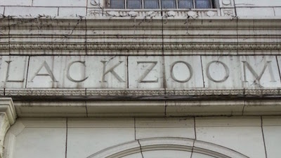 "Terra cotta tile reading ""Lackzoom"""