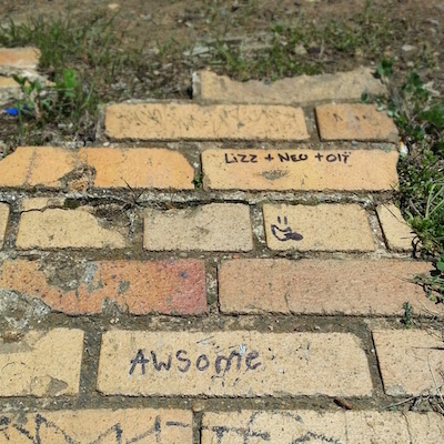 "bricks embedded in grass and dirt with handwritten ""awsome"" graffiti"