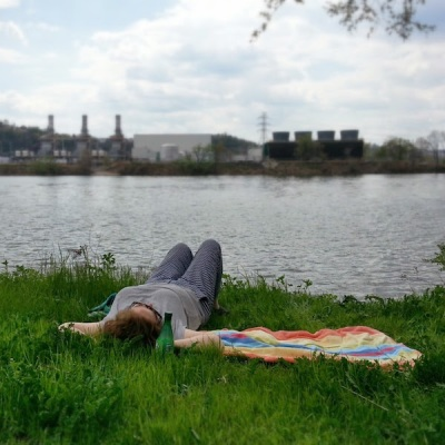 woman laying on grass by the Ohio River