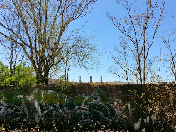 cement wall with graffiti, trees, and smokestacks in the distance