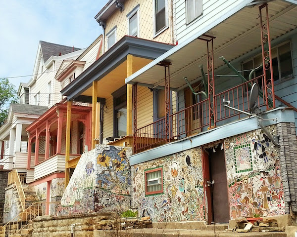 A row of frame houses with mosaics covering the basement/foundation walls, Pittsburgh, Pa.