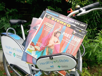 Healthy Ride bicycle with vinyl records spilling out of its small cargo basket.