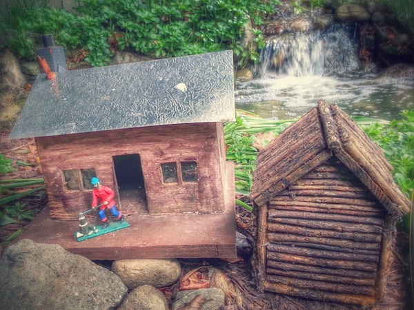 model log cabins with waterfall in background