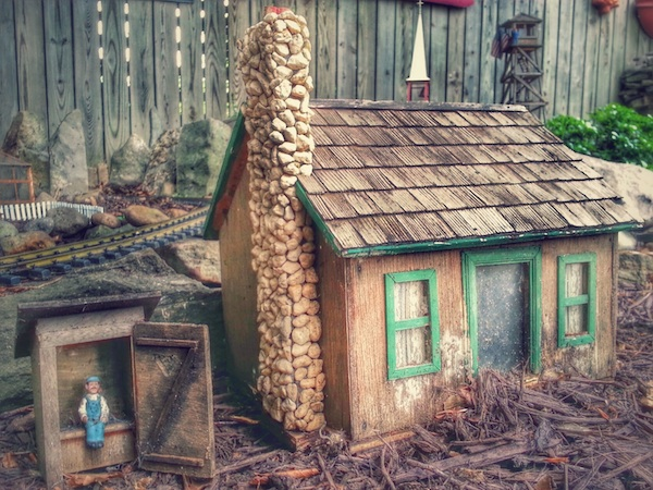 model cabin with man in outhouse