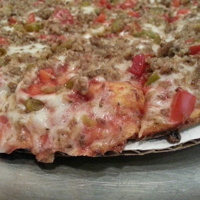close-up of Sir Pizza sausage and pepper pizza crust