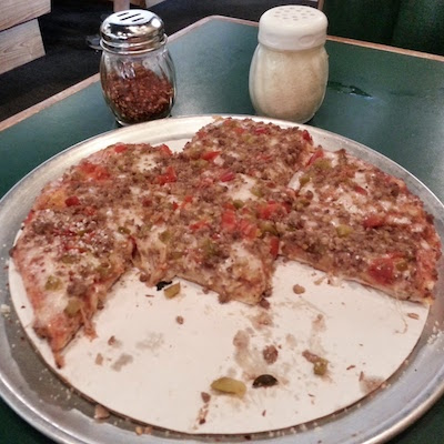 """half-eaten Sir Pizza 10"""" pizza with sausage and peppers"""