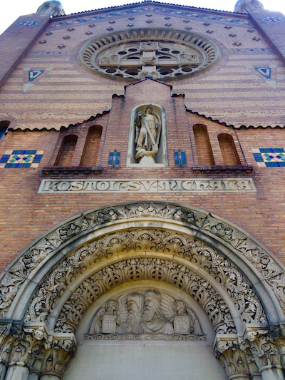 Front of St. Michael Church featuring tympanum, figure in a niche, and rose window