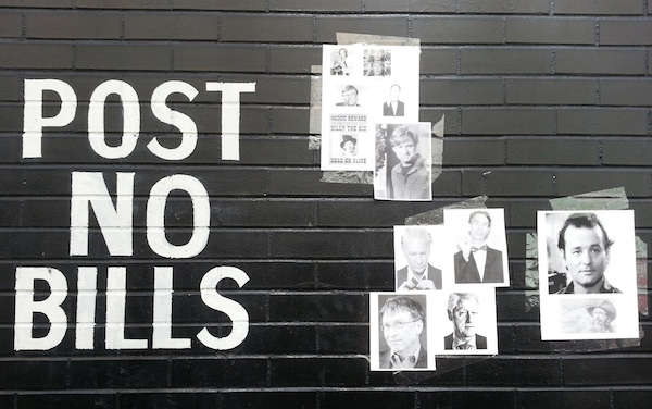 """brick wall painted with """"Post No Bills"""" message plus print-outs of famous Bills taped to the wall, Pittsburgh, PA"""