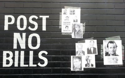 "brick wall painted with ""Post No Bills"" message plus print-outs of famous Bills taped to the wall, Pittsburgh, PA"