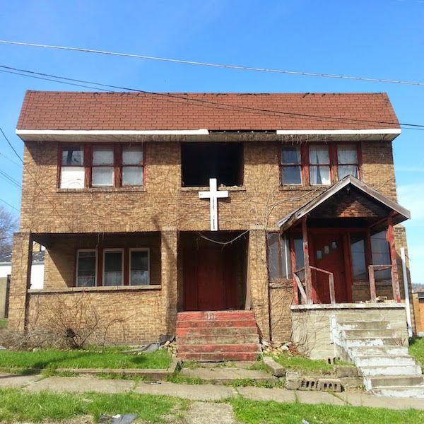Run down brick house with large white cross above entryway, Steubenville, Ohio