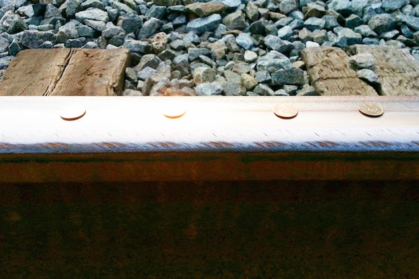 Four pennies lying on a train track