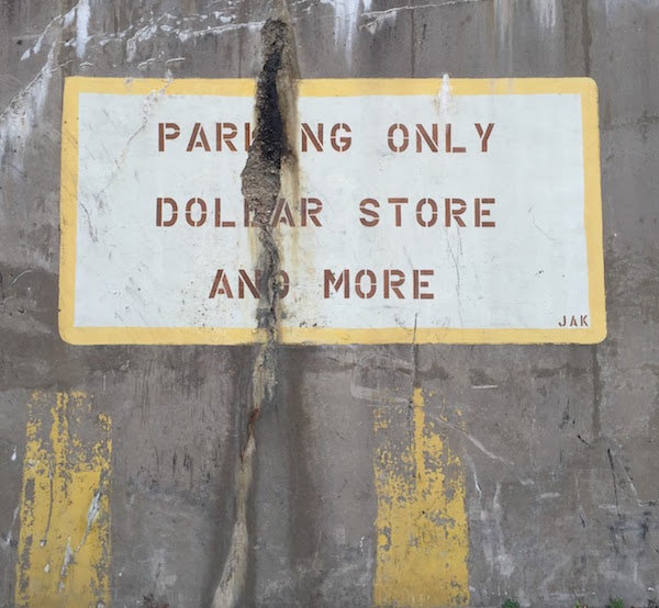 "hand-painted sign on cement wall reading ""Parking only Dollar Store and More"""