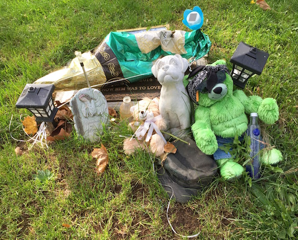 grave with teddy bears, solar lights, and deflated champagne bottle balloon