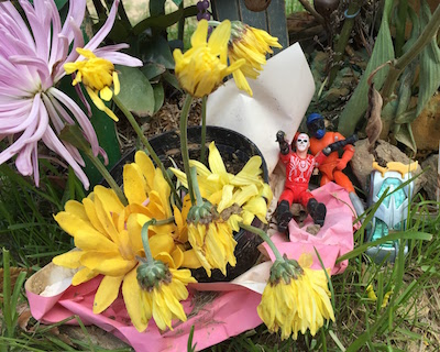 two plastic action figures with living flowers