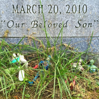 four plastic action figures in weeds in front of gravestone with date and epitaph