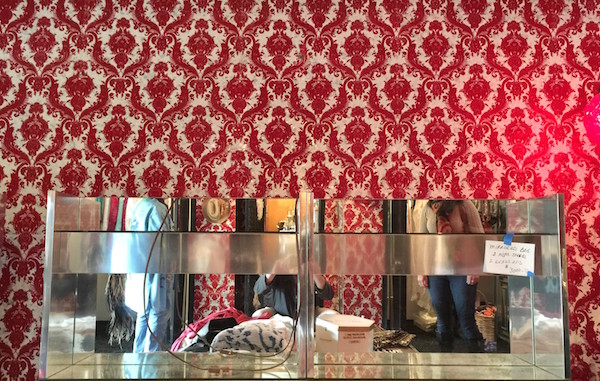 mirrored headboard against a very complex wallpaper pattern