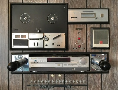 wall-mounted sound system including reel-to-reel tape deck, 8-track player, intercom, CD player, speaker toggle switches