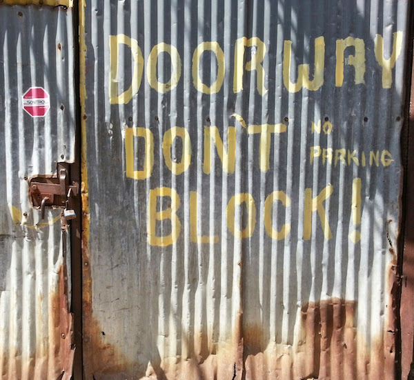 corrugated metal doors with hand-painted no parking message