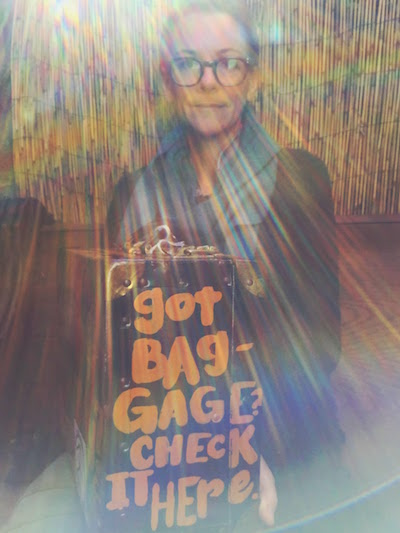 "Daria Sandburg holding metal case with painted words ""Got baggage? Check it here."""