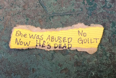 "torn paper scrap with the writing ""She was abused, now he's dead. No guilt."""