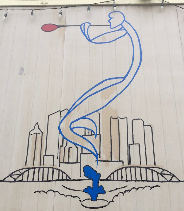 Mural of a spirit blowing glass above the Pittsburgh skyline at Gallery G Glass, Pittsburgh, PA