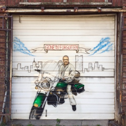 """Mural painted on garage door of man on motorcycle with the Pittsburgh skyline behind him and a banner reading """"Gone but not Forgotten"""""""