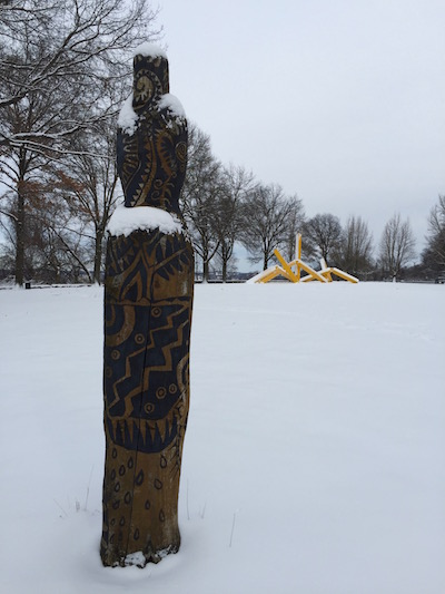 "Wooden Persephone Project sculpture in snow with John Raymond Henry ""Pittsburgh"" (aka ""The French Fry sculpture"") in background, Frank Curto Park, Pittsburgh, PA"