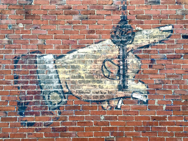ghost sign of hand with extended index finger and shirt cuff painted on brick wall, Glassport, PA