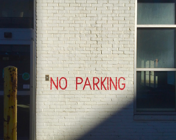 "white brick wall with ""NO PARKING"" painted in red, Pittsburgh, PA"