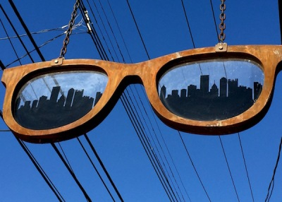 Chromos Eyewear sign of a large pair of glasses, with the Pittsburgh skyline in each lens