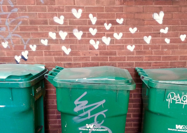 graffiti on brick wall of dozens of small hearts above a row of commercial trash bins, Pittsburgh, PA