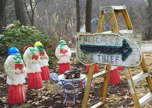 "Handmade wooden sign with arrow reading ""Neighbor is a Thief"" with choir member lawn ornaments missing heads, Ross Township, PA"