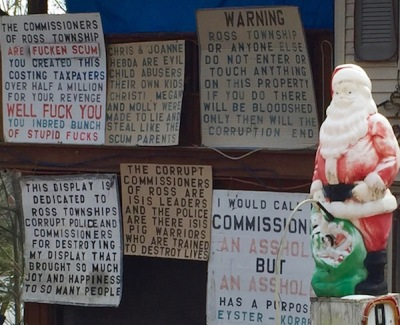 Santa Claus lawn ornament with protest signs against Ross Township leadership