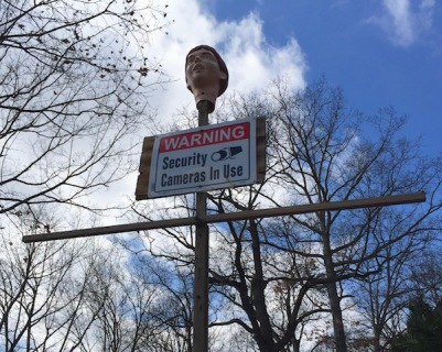 "Plastic head on cross with ""Security cameras in use"" sign, Ross Township, PA"