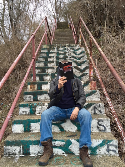 The Dirty Poet sits on a set of Pittsburgh city steps with his face hidden behind an open copy of his book
