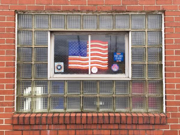 Neon American flag in glass block window of brick building
