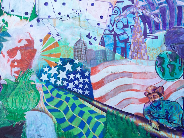Mural detail showing waving abstract American flag with many other design elements including dice, city skyline, men, flowers, etc.